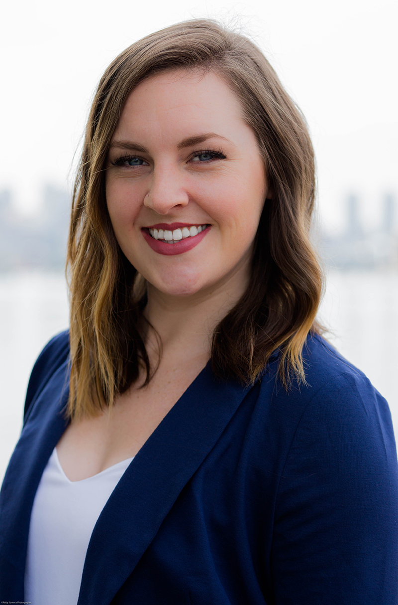 Female wearing a navy blue blazer and white top with the Seattle skyline in the background