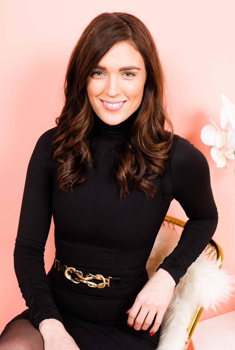 Dark haired girl wearing a black turtleneck dress with a gold belt buckle