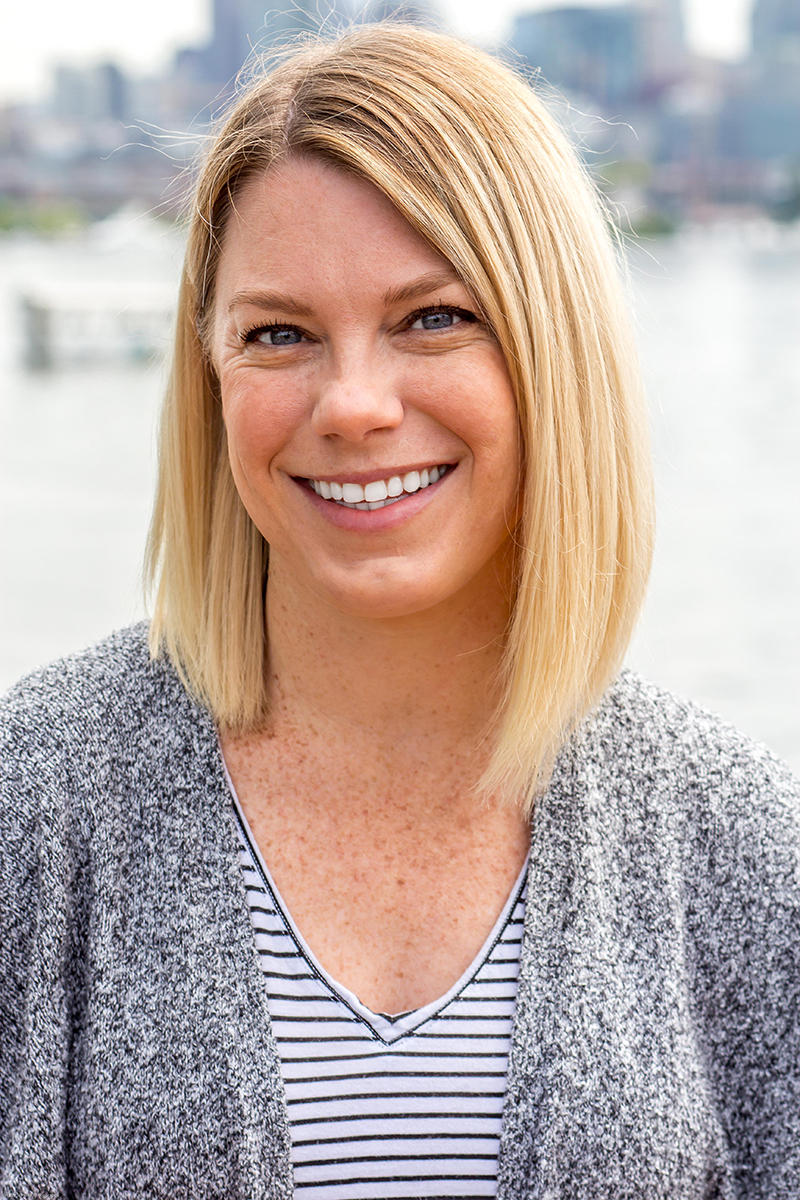 Blonde female wearing a grey sweater and a striped shirt with water in the background