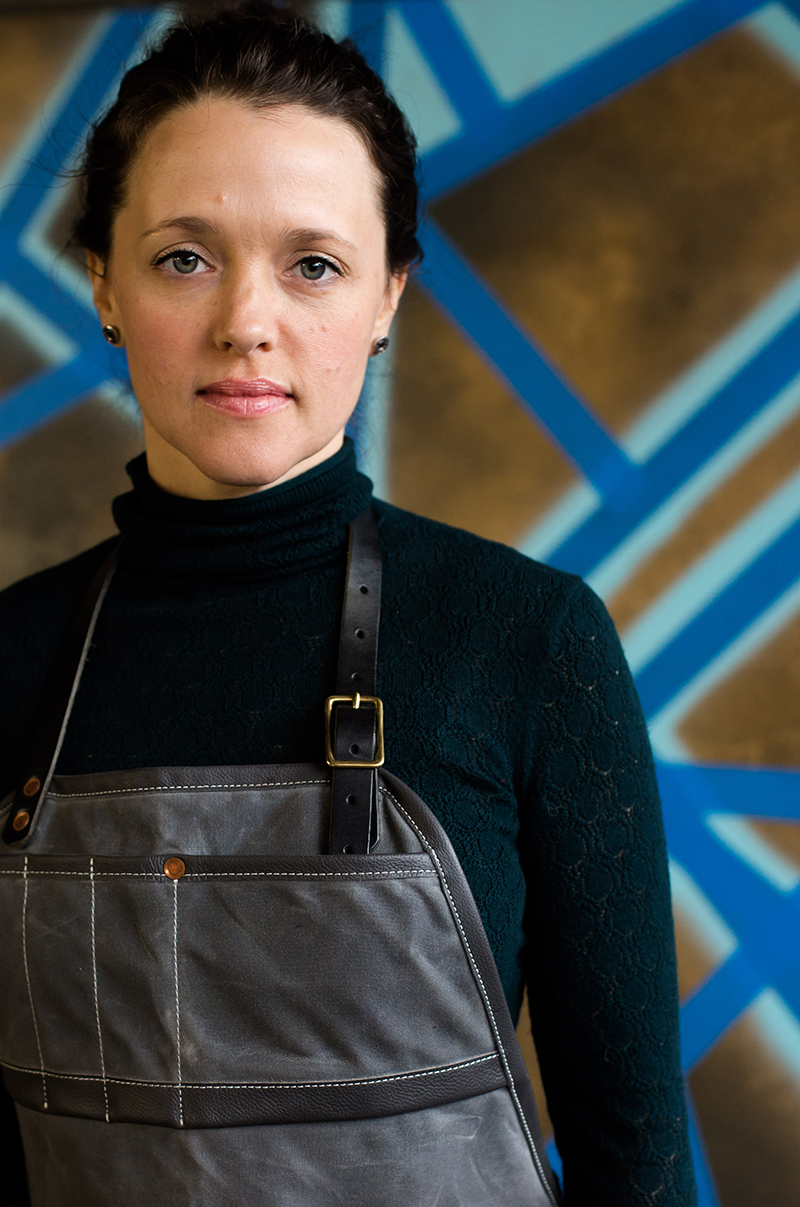 Female artist wearing a black turtleneck and black leather apron in front of her art