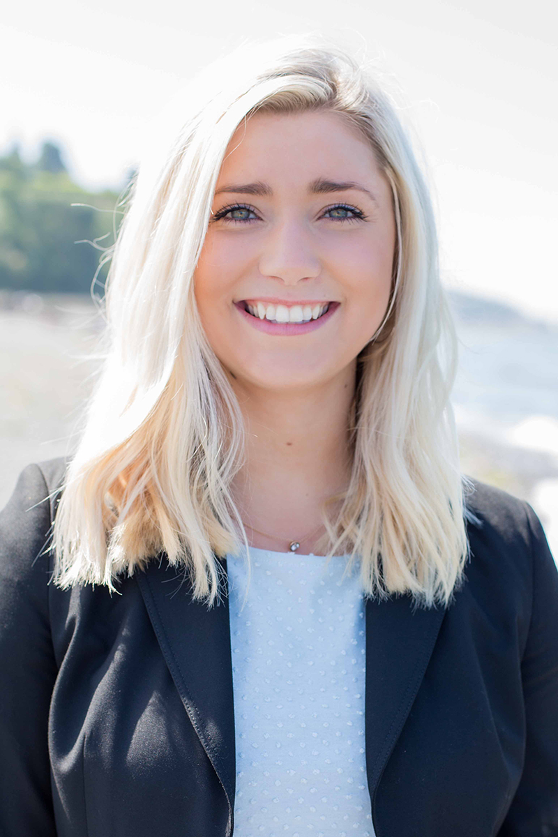 Blonde female wearing a black blazer and white top on the beach in Edmonds