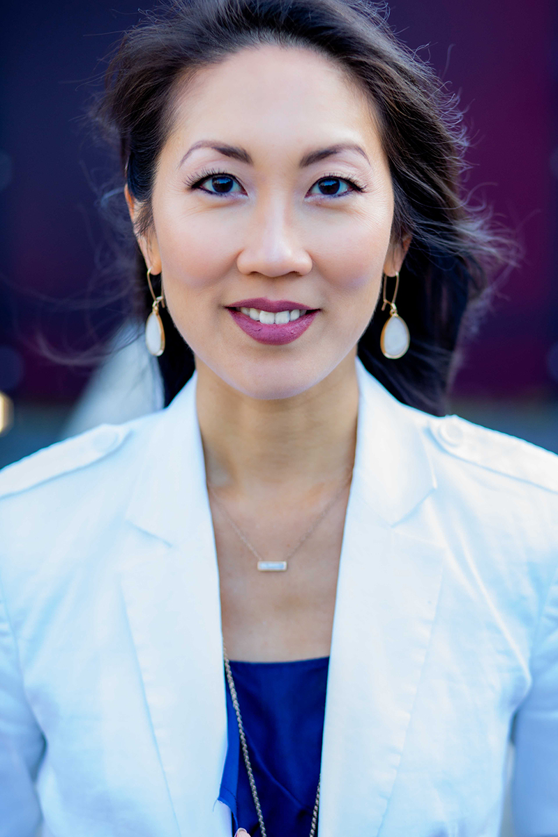 Asian Female wearing a white blazer and teardrop earrings at the Januik Winery in Woodinville
