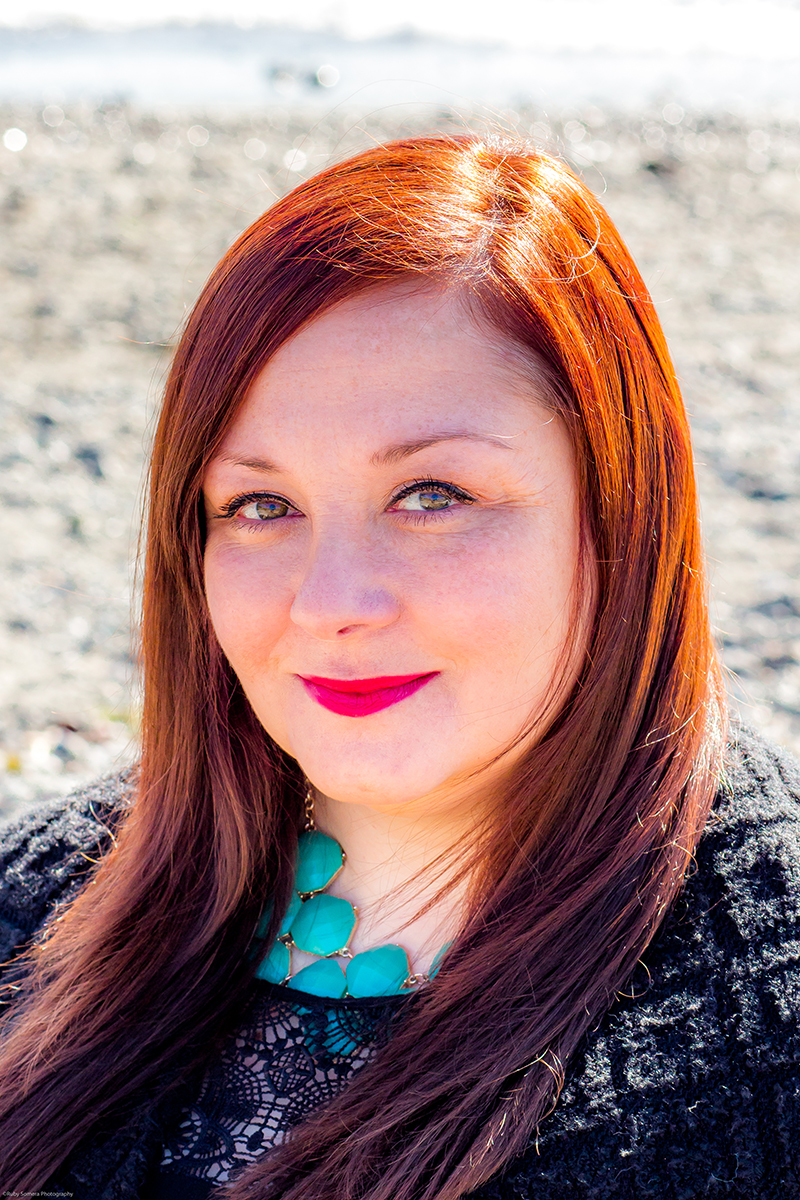 Red-haired girl wearing red lipstick and a turquoise necklace on the Beach in Edmonds