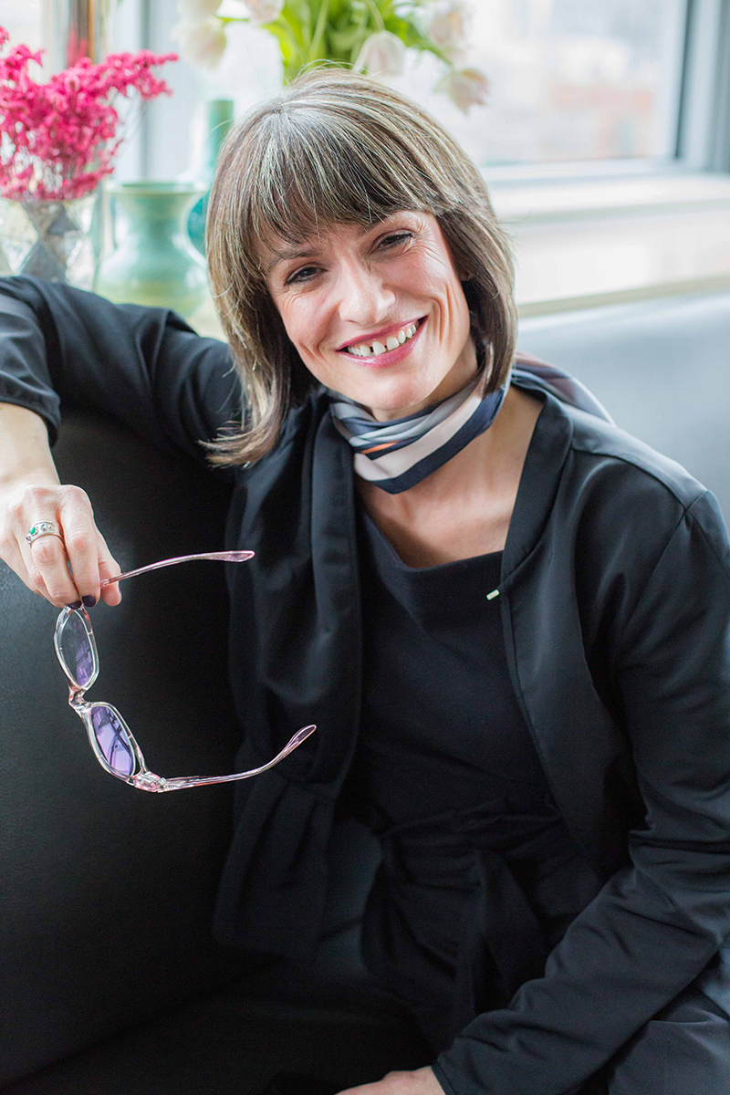 Middle Aged Female holding her glasses with a bob and bangs and a gap between her teeth