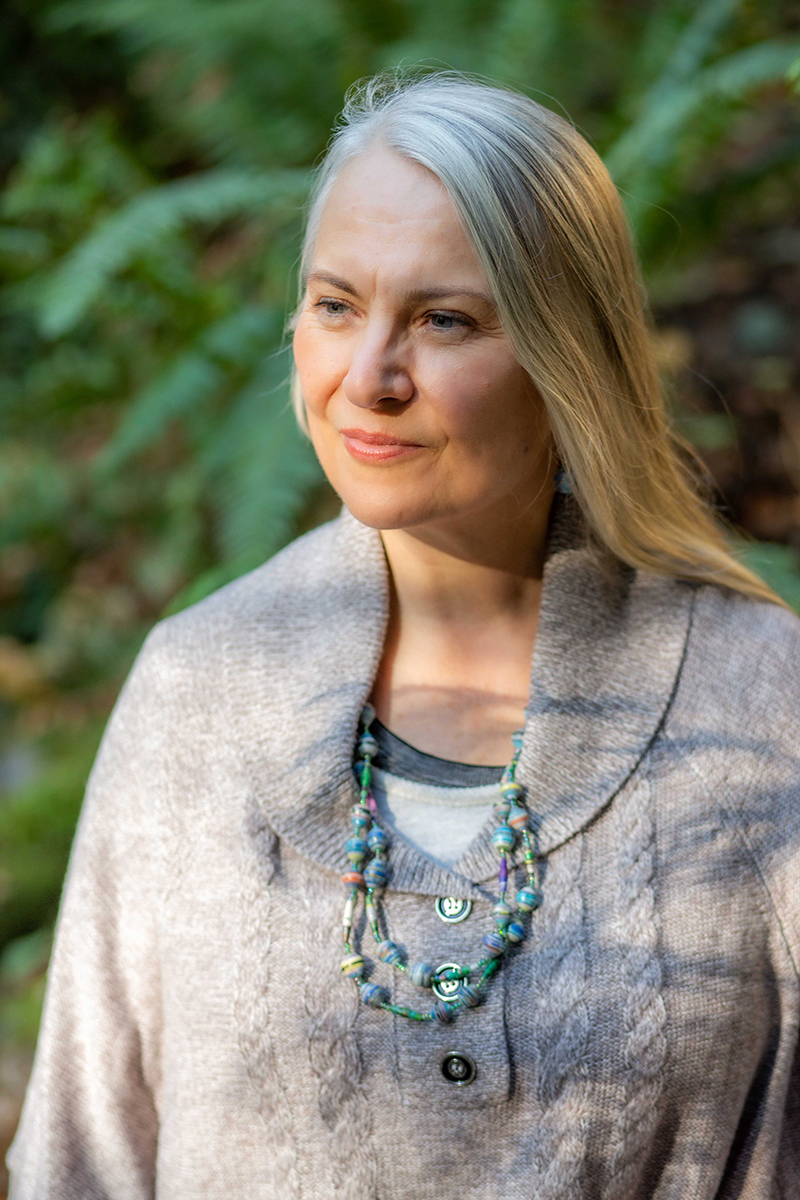 Caucasian woman in gray sweater with a blue beaded necklace