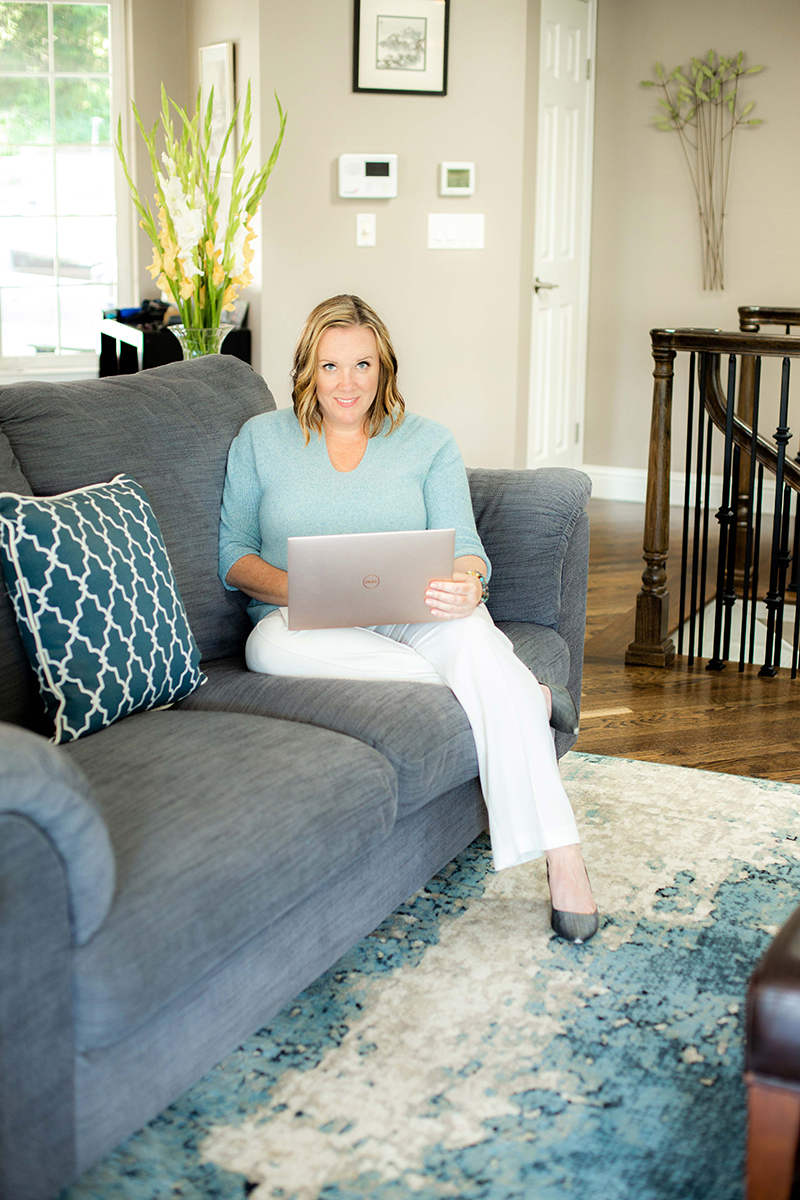 caucasian woman sitting on couch with a laptop