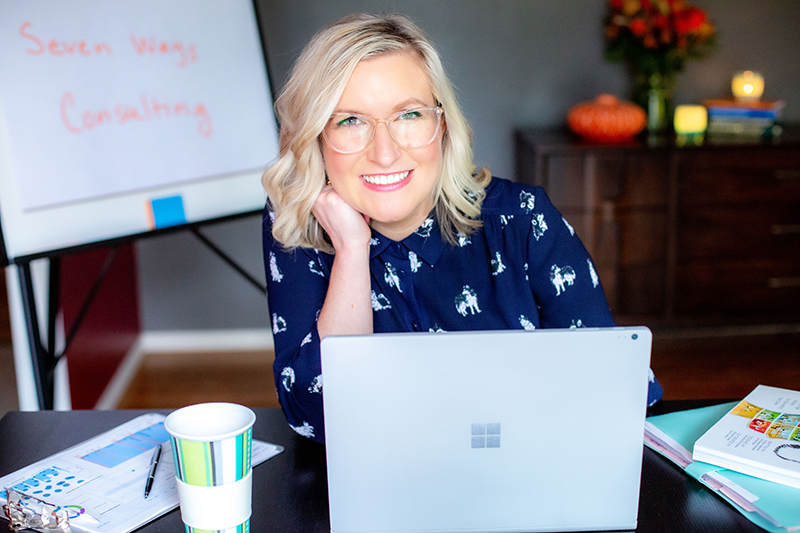 Caucasian blonde woman wearing glasses and smiling while working on her laptop.