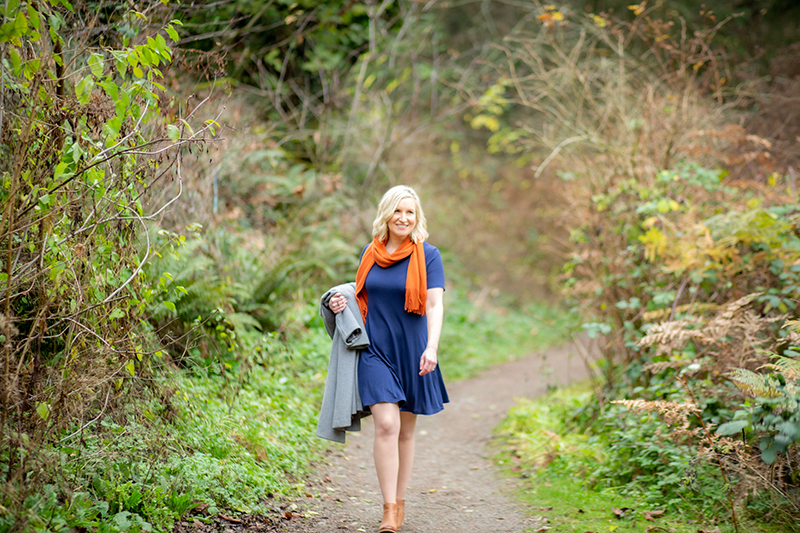 Blonde Caucasian woman in a navy blue dress and orange scarf walking down a trail