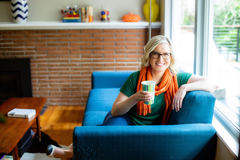 Caucasian blonde woman drinking coffee on blue sofa.